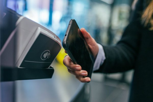 Kvinne som betaler kontaktløst, kontaktløs betaling, betaling, NFC, nærfeltkommunikasjon, tæppe, å tappe, kvinne som tæpper, betal kontaktløst, betalingsterminal, kortterminal